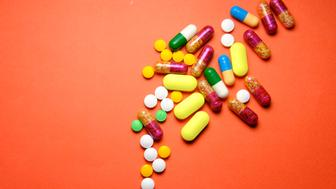 colourful pills spilled on blue background.