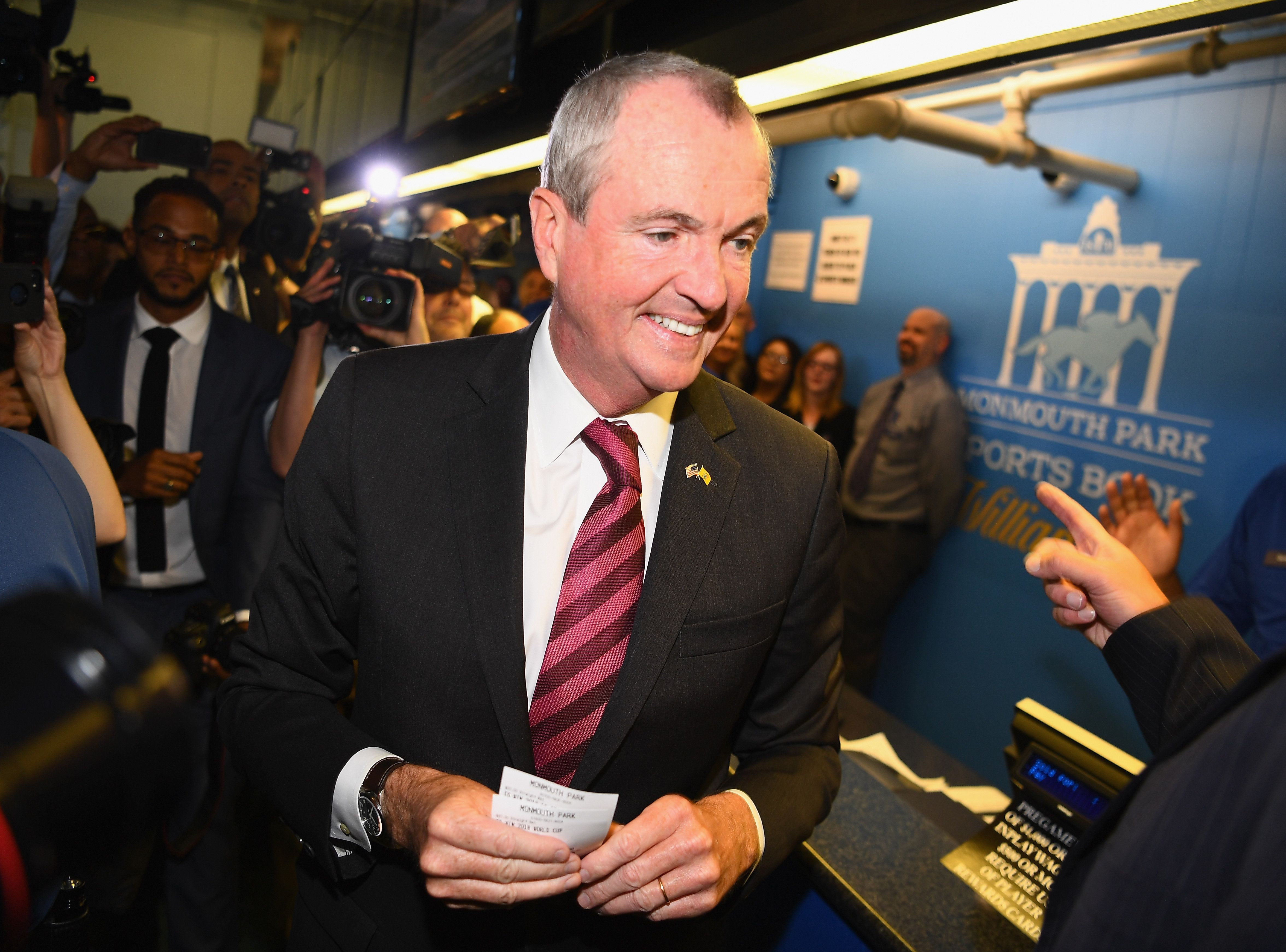 OCEANPORT, NJ - JUNE 14:  Governor of New Jersey Phil Murphy places the first bet at the William Hill Sports Book at Monmouth Park as it opens and welcomes public to place first legal sports bets on June 14, 2018 in Oceanport, New Jersey.  (Photo by Dave Kotinsky/Getty Images for  William Hill Race & Sports Bar )