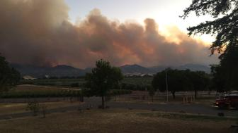 Smoke rises in distance from County Fire near County Road 63 and Highway 16 in Rumsey Canyon in this #CountyFire image on social media in Brooks, California, U.S., July 2, 2018.   Courtesy California Department of Forestry and Fire Protection/Handout via REUTERS  ATTENTION EDITORS - THIS IMAGE HAS BEEN SUPPLIED BY A THIRD PARTY.
