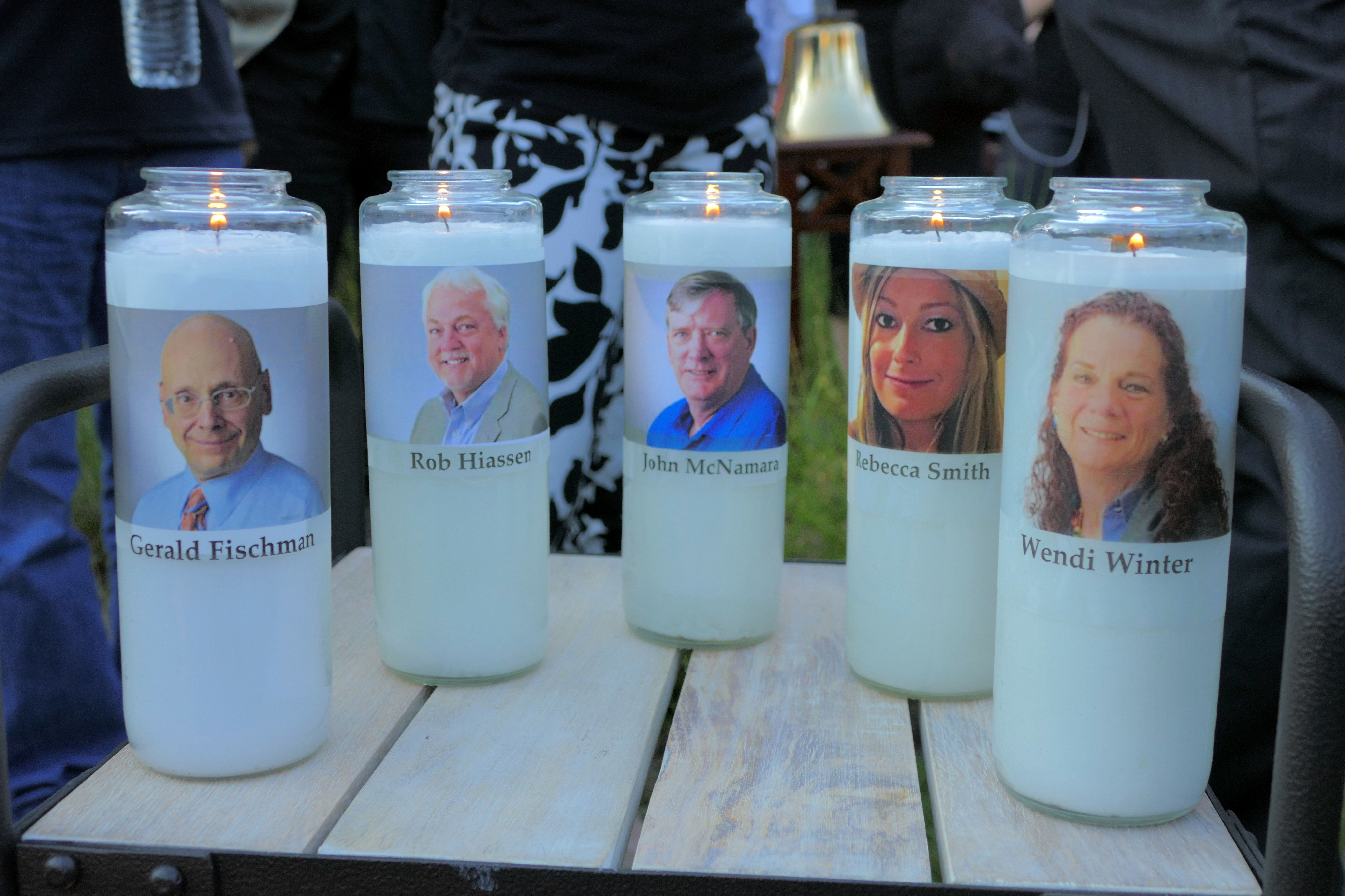 Candles honoring Gerald Fischman, Rob Hiassen, John McNamara, Rebecca Smith, and Wendi Winters flicker as the sun sets during a candlelight vigil on Friday, June 29, 2018, at Annapolis Mall for the five Capital Gazette employees slain during a shooting spree in their newsroom. (Karl Merton Ferron/Baltimore Sun/TNS via Getty Images)