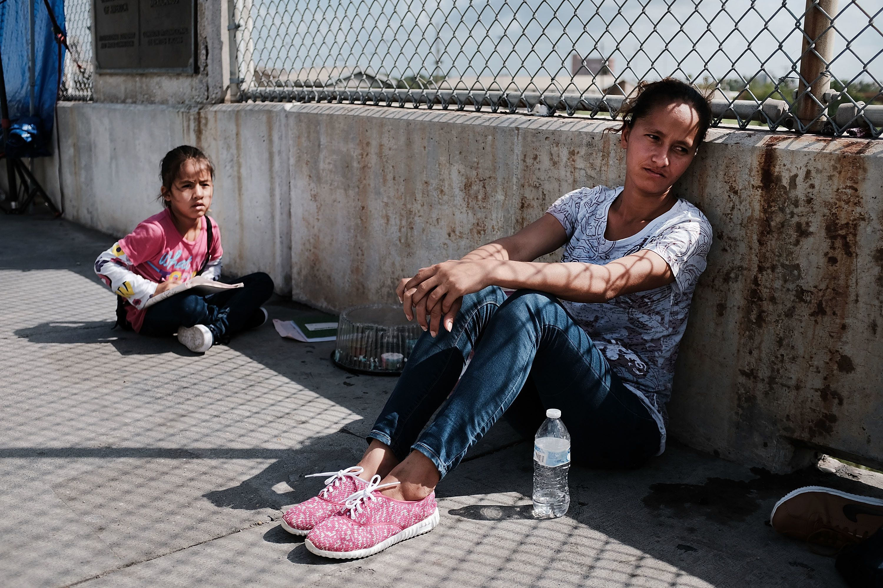 BROWNSVILLE, TX - JUNE 25:  A Honduran woman, fleeing poverty and violence in her home country, waits along the border bridge with her family after being denied entry into the U.S. from Mexico on June 25, 2018 in Brownsville, Texas. Immigration has once again been put in the spotlight as Democrats and Republicans spar over the detention of children and families seeking asylum at the border. Before President Donald Trump signed an executive order last week that halts the practice of separating families who are seeking asylum, more than 2,300 immigrant children had been separated from their parents in the zero-tolerance policy for border crossers.  (Photo by Spencer Platt/Getty Images)
