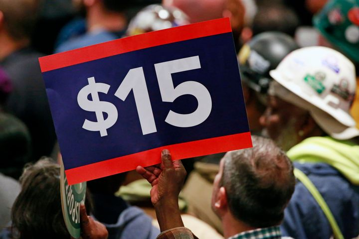 A supporter holds a sign while listening to Hillary Clinton speak at a rally inApril 2016 to celebrate New York increasing the minimum wage to $15 an hour.
