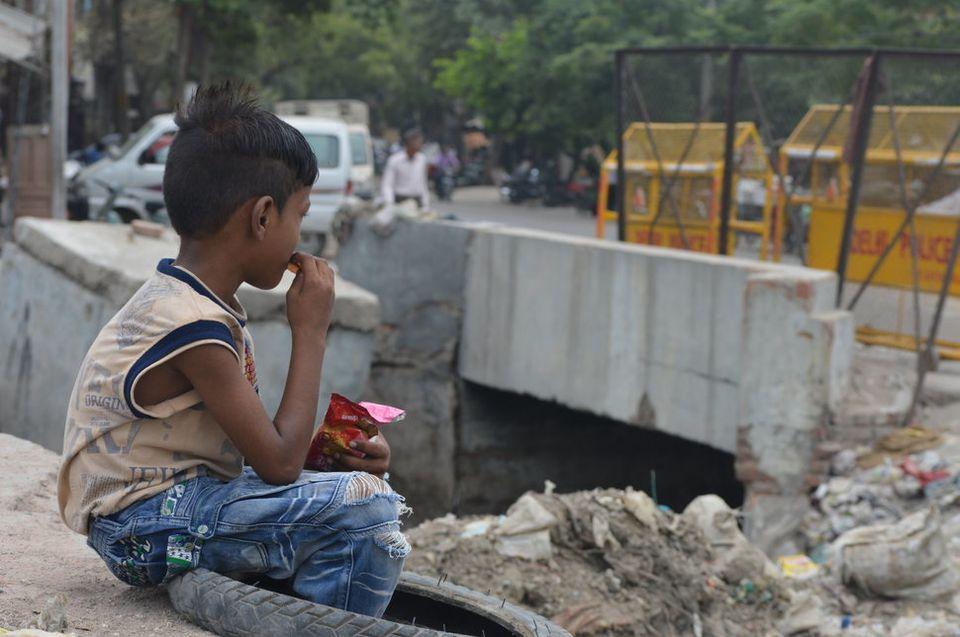 Ein Junge isst am Abwasserkanal bei Kanti Nagar in