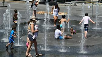 Women and children play in the water fountains at the Place des Arts in Montreal, Canada on a hot summer day July 3, 2018. (Photo by EVA HAMBACH / AFP)        (Photo credit should read EVA HAMBACH/AFP/Getty Images)