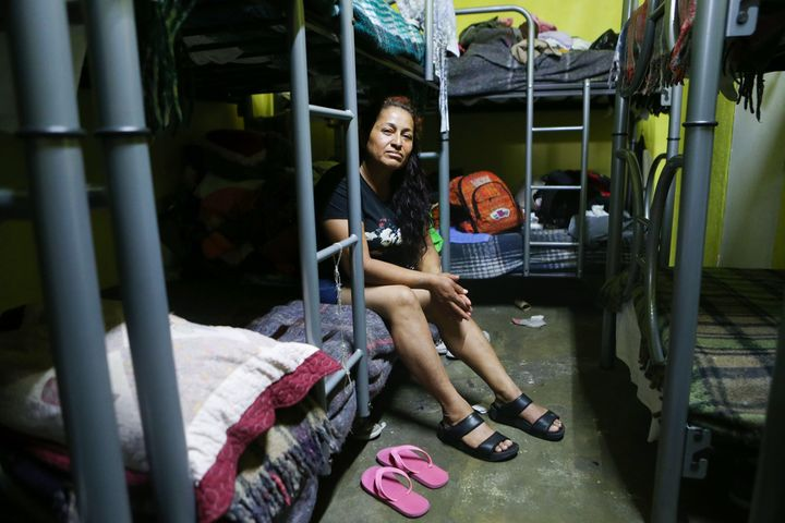 A migrant mother of three, from western Mexico, poses while sitting on her bed in the room where women and children sleep in
