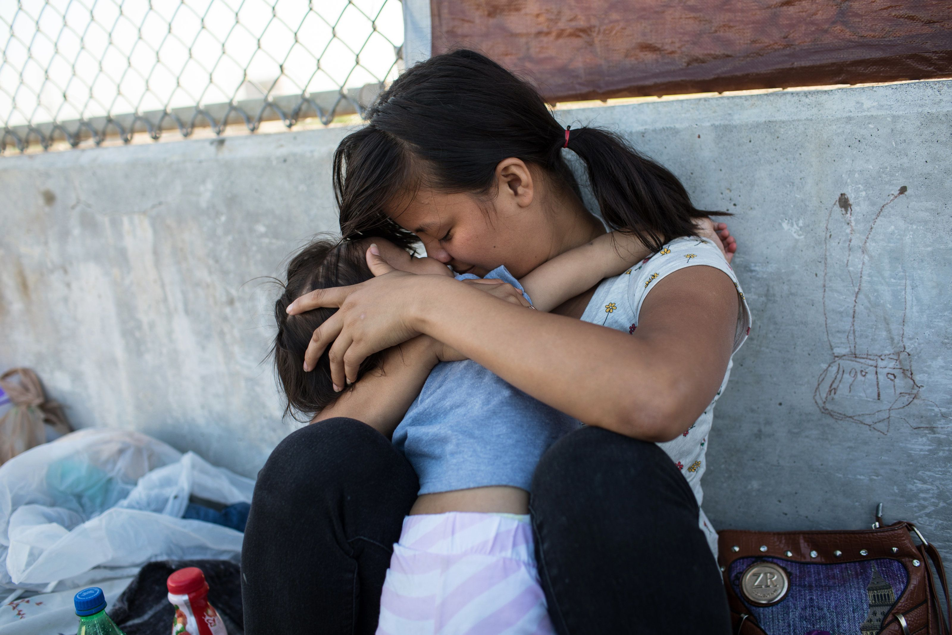 MATAMOROS, MX - JUNE 28: A Honduran woman embraces her 2-year-old daughter as they wait on the Mexican side of the Brownsvill