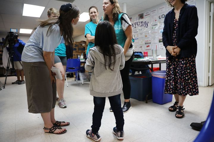 Jenquel, who recently crossed the U.S.-Mexico border with her mother and siblings, speaks with volunteers at the Catholic Cha