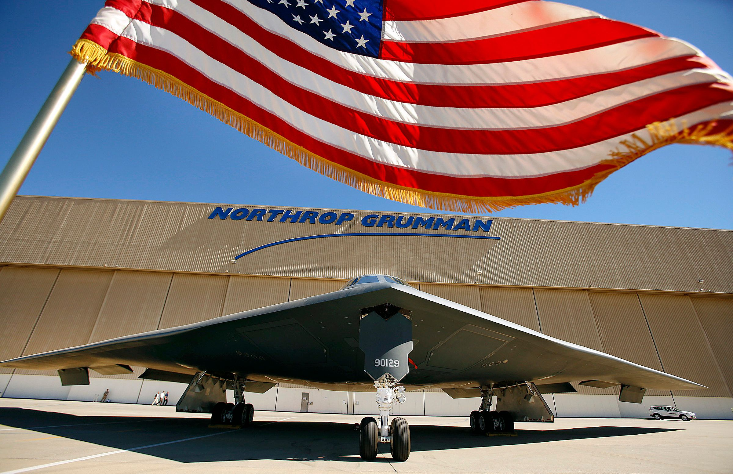 PALMDALE, CA  JULY 17, 2014 -- The US flag flies near the U.S. Air Force's B-2 Spirit Stealth bomber 'Spirit of Georgia' at the Northrop Grumman Corp. facility at U.S. Air Force Plant 42 in Palmdale on July 17, 2014 as Northrop Grumman hosts the 25th anniversary celebration of the first flight in the same location at the Palmdale Aircraft Integration Center of Excellence at U.S. Air Force Plant 42. Just as they had on that historic day 25 years ago, several hundred Northrop Grumman employees, civic leaders and Air Force personnel stood along the fence line in Palmdale to watch a B-2 stealth bomber taxi onto the runway for flight following the ceremony.  (Photo by Al Seib/Los Angeles Times via Getty Images)
