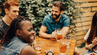 Multi-ethnic group of people meat at the pub to relax, drink beer, socialize, have fun.