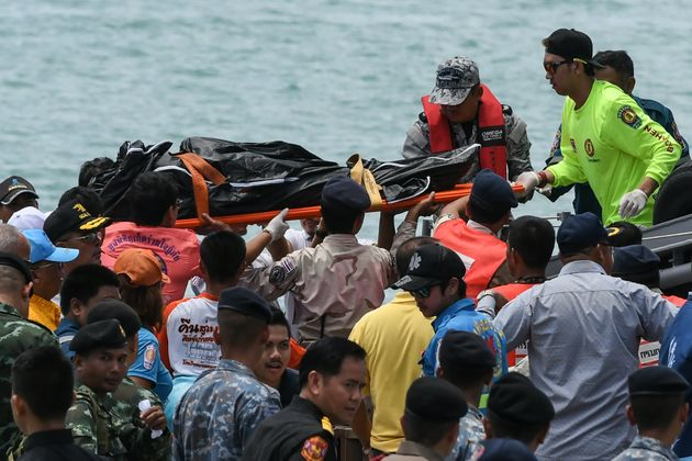 Thai rescue personnel carry a body bag bearing the recovered body of a