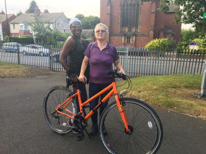Cycle instructor, Catherine, and a participant, Janice, support women as they gain the skills to get on their bikes.