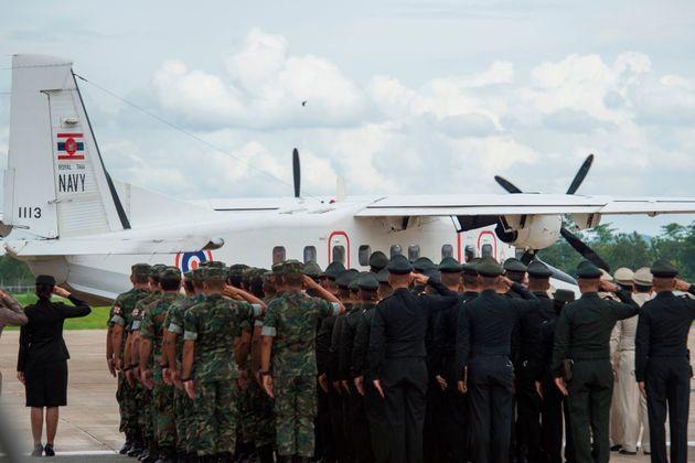 Des soldats thaïlandais et des officiers de police saluent l'avion de la marine thaïlandaise...