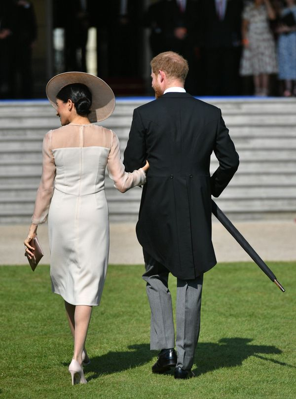 Harry and Meghan walk together at the Prince of Wales' 70th Birthday Patronage Celebration at Buckingham Palace on