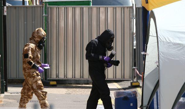 Investigators in chemical suit work behind screens erected in Rollestone Street, Salisbury, Wiltshire.