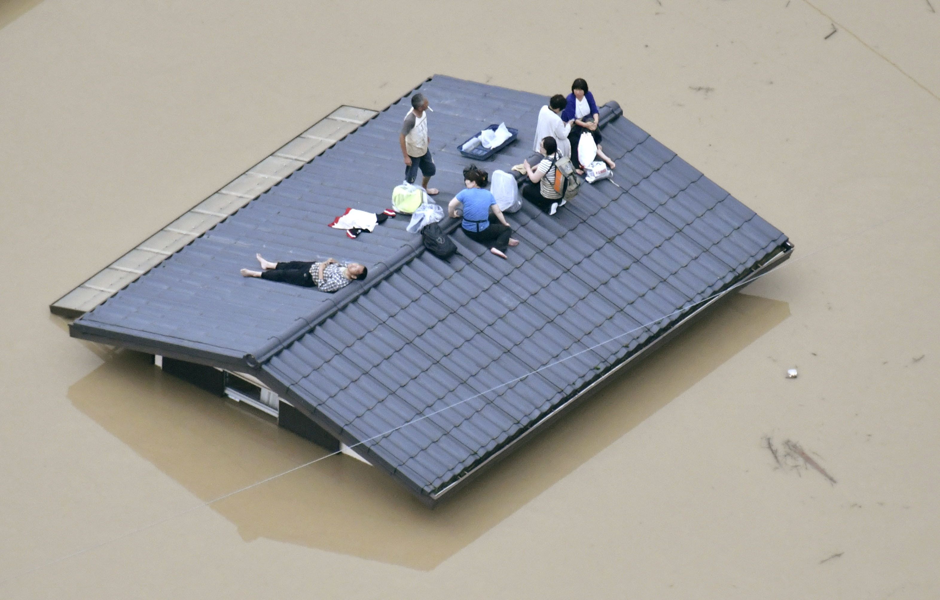 An aerial view shows local residents on the roof of asubmerged housein a flooded area as they wait to be rescued
