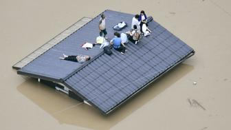 An aerial view shows local residents seen on the roof of submerged house at a flooded area as they wait for a rescue in Kurashiki, southern Japan, in this photo taken by Kyodo July 7, 2018. Mandatory credit Kyodo/via REUTERS ATTENTION EDITORS - THIS IMAGE WAS PROVIDED BY A THIRD PARTY. MANDATORY CREDIT. JAPAN OUT. NO COMMERCIAL OR EDITORIAL SALES IN JAPAN.     TPX IMAGES OF THE DAY