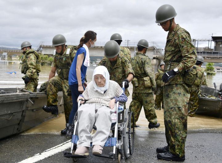 An elderly man in a wheelchair rescued from a flooded area in Kurashiki on July 8, 2018.