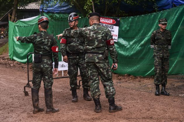Thai soldiers speak at the Tham Luang cave area as operations continue for the 12 boys and their coach...
