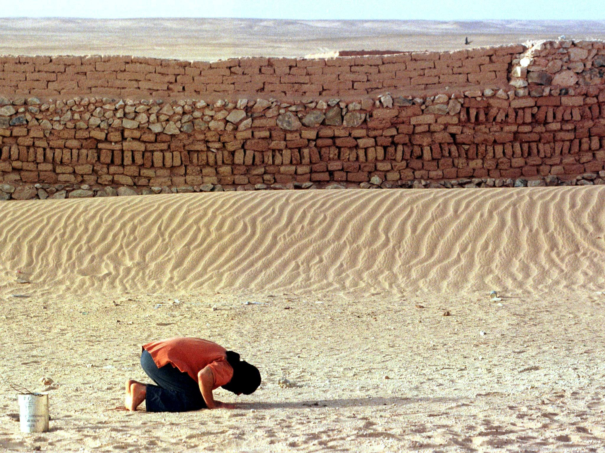 A Moroccan prisoner of war prays beside the wall of a Saharawi prison in the Algerian