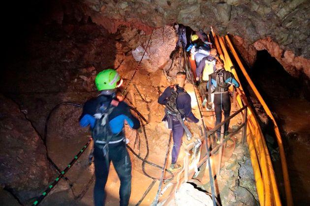 Thai rescue team members walk inside the