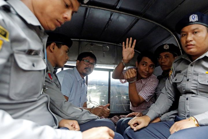 Detained Reuters journalist Wa Lone and Kyaw Soe Oo sit beside police officers as they leave Insein court in Yangon, Myanmar,