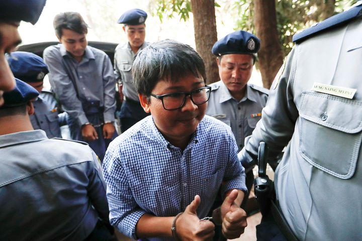 Journalist Wa Lone gives two thumbs up while being escorted by police into a court hearing back in February. Fellow journalis