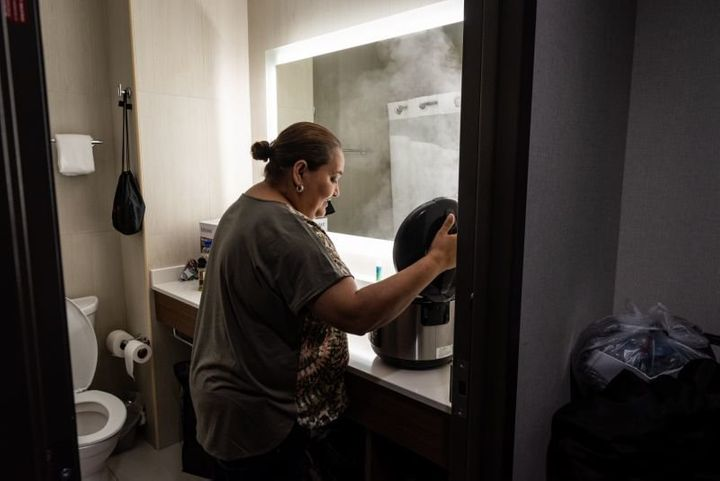 Jenyffer Ortiz cooks chicken in a rice cooker in the hotel bathroom, where there is counter space. She cooks for herself to b