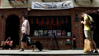 People are see in front of The Stonewall Inn, on the eve of the LGBT Pride March, in the Greenwich Village section of New York City, U.S. June 24, 2017. REUTERS/Brendan McDermid