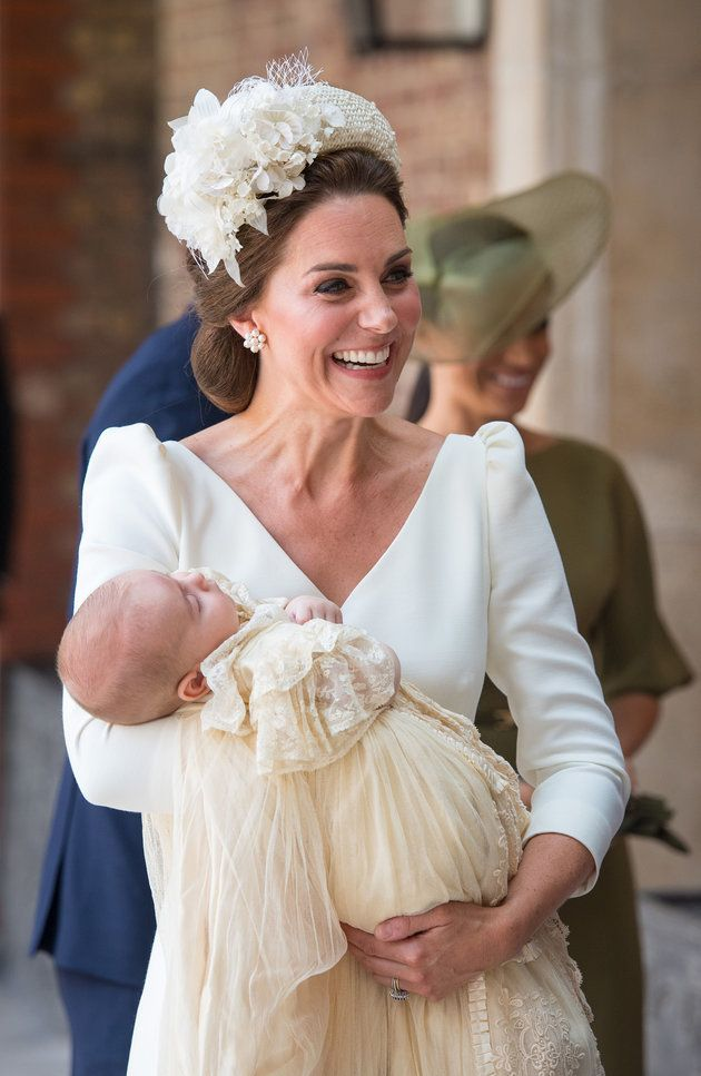 The Duchess of Cambridge carries Prince Louis.