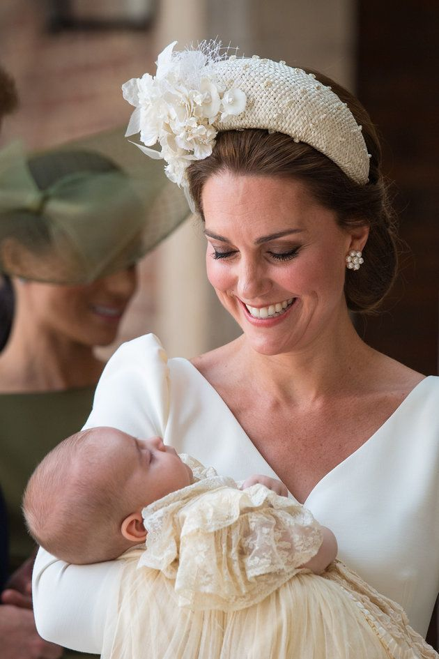 The Duchess of Cambridge holding Prince Louis, with Meghan, Duchess of Sussex in the background.