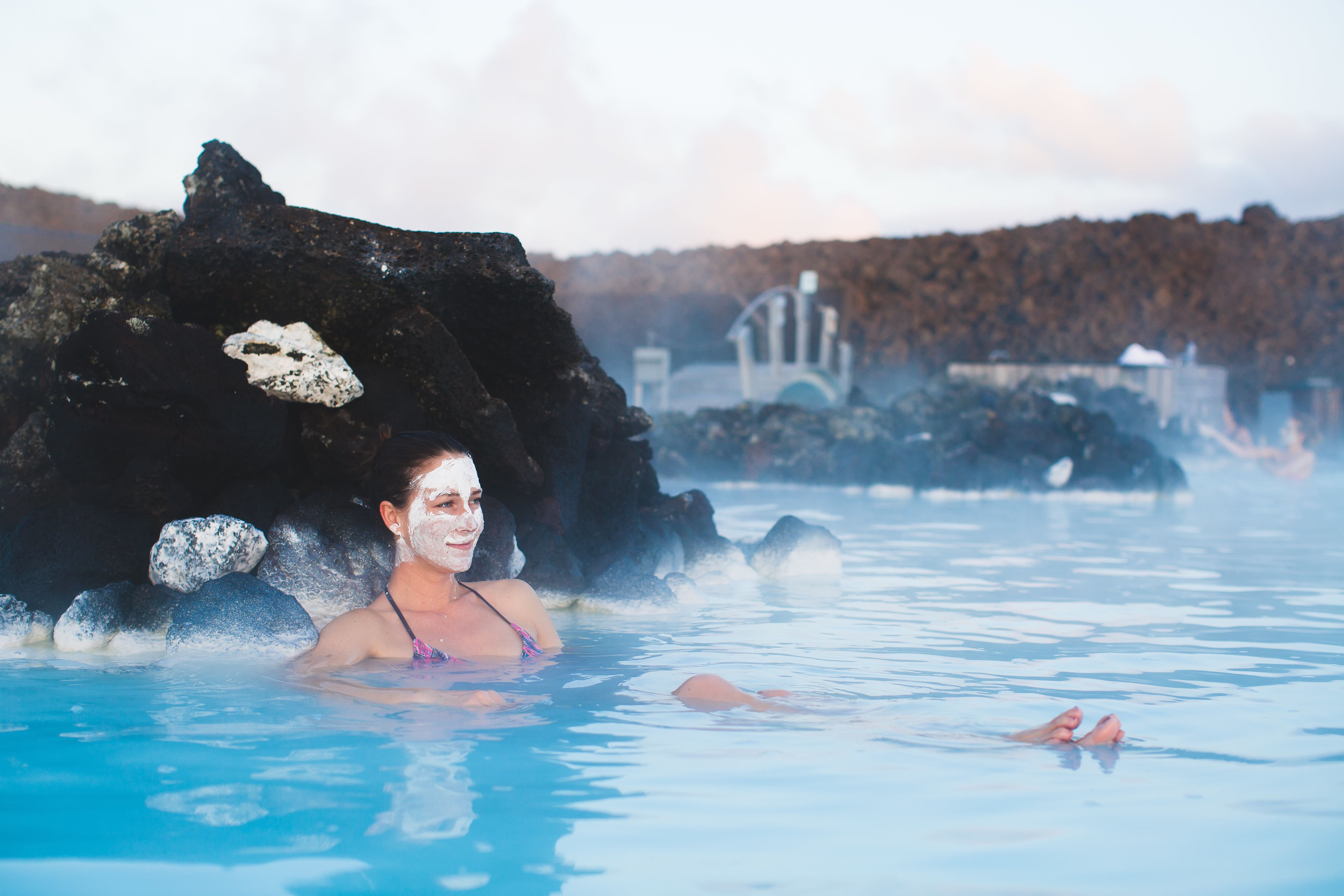Woman relaxing in geothermal spa in hot spring pool in Iceland. Girl enjoying bathing in a blue water lagoon with famous healing mud on her face.