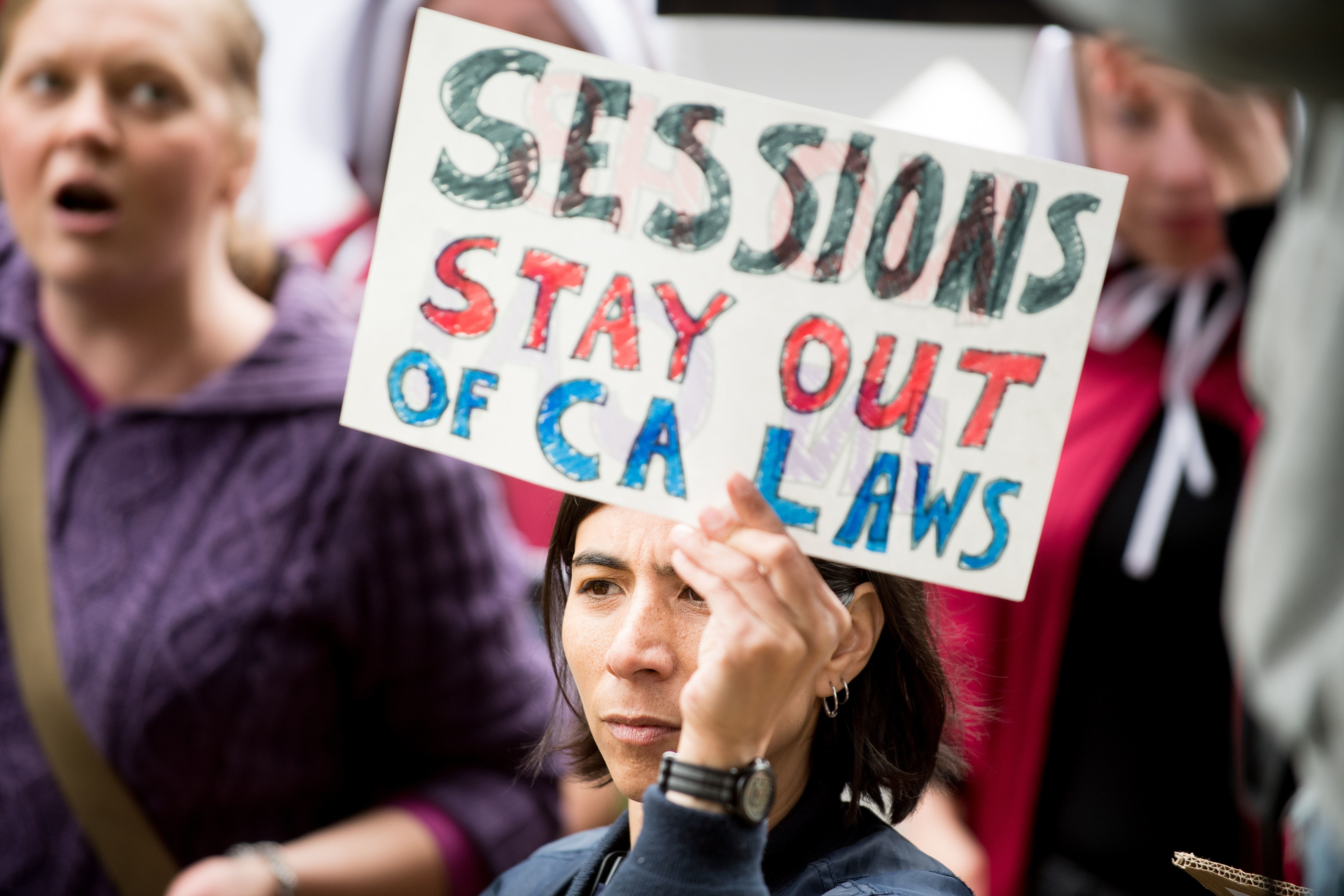 People protest outside a speech by US Attorney General Jeff Sessions March 7, 2018, in Sacramento, California. Sessions admonished California politicians for not cooperating with federal authorities on immigration enforcement issues. US Attorney General Jeff Sessions warned California Wednesday that the federal government would use all its legal powers to fight protections provided unauthorized immigrants, a day after suing the state over its sanctuary laws.'California is using every power it has -- and some it doesn't -- to frustrate federal law enforcement. So you can be sure I'm going to use every power I have to stop them,' Sessions told law enforcement officials in Sacramento.  / AFP PHOTO / NOAH BERGER        (Photo credit should read NOAH BERGER/AFP/Getty Images)