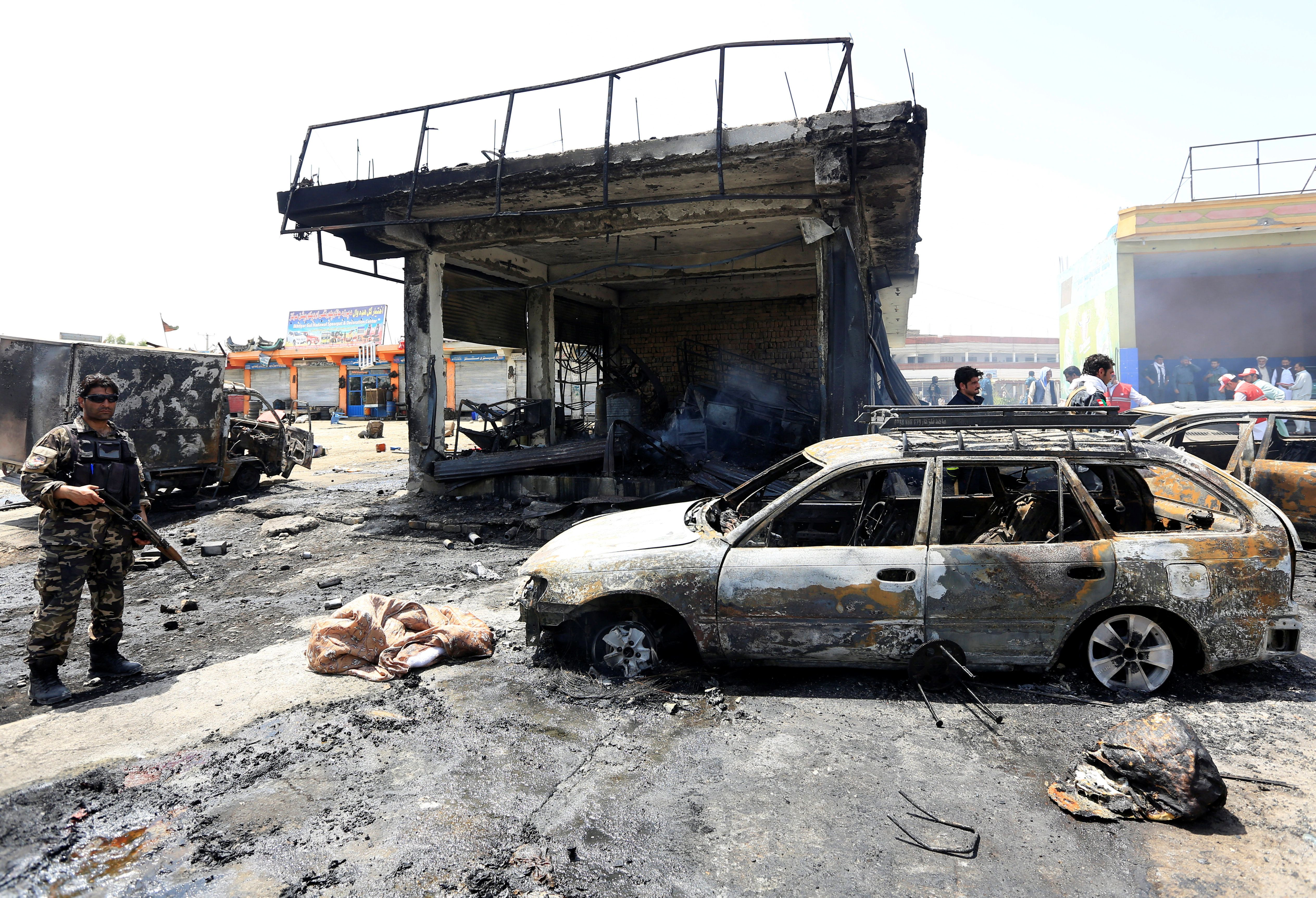Afghan security forces inspect the site of a suicide attack in Jalalabad, Afghanistan on Tuesday.