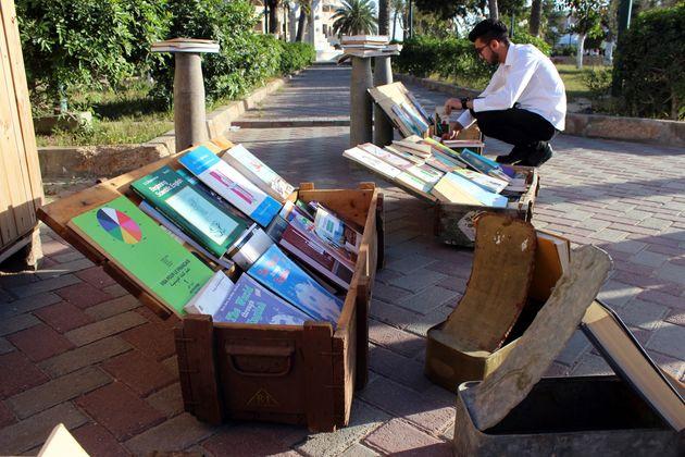 Un hommefeuillettedes livres exposés dans des boîtes utilisées pour garder...