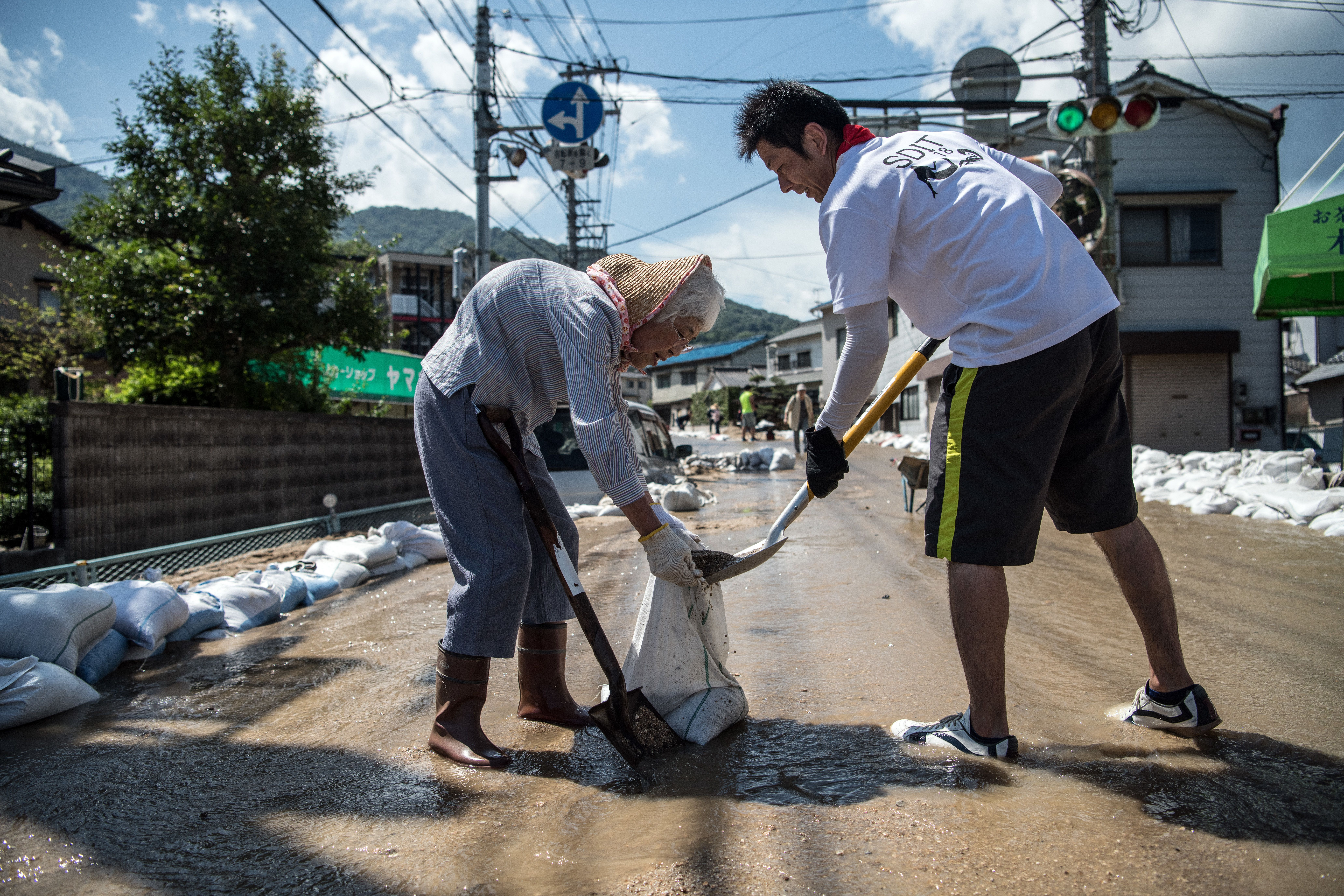 HIROSHIMA, JAPAN - JULY 10: An elderly lady helps clear a road following a landslide, on July 10, 2018 in Yanohigashi near Hiroshima, Japan. Over 112 people have died and 78 are missing following floods and landslides triggered by 'historic' levels of heavy rain across central and western parts of Japan while more than 73,000 rescuers are racing to find survivors as temperatures rise. Japan's Prime Minister Shinzo Abe warned on Sunday of a 'race against time' to rescue flood victims as almost 2 million people are subject to evacuation orders and tens of thousands remain without electricity and water. (Photo by Carl Court/Getty Images)