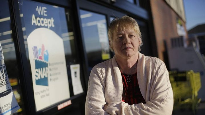 A woman stands outside a store that accepts food stamps in Bon Aqua, Tennessee. The farm bill being considered in Congress co