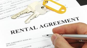rental agreement form with signing hand and pen and keys