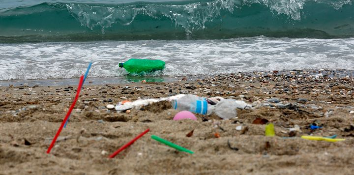 Plastic garbage, including straws, lies on the Aegean Sea beach near Athens, Greece.