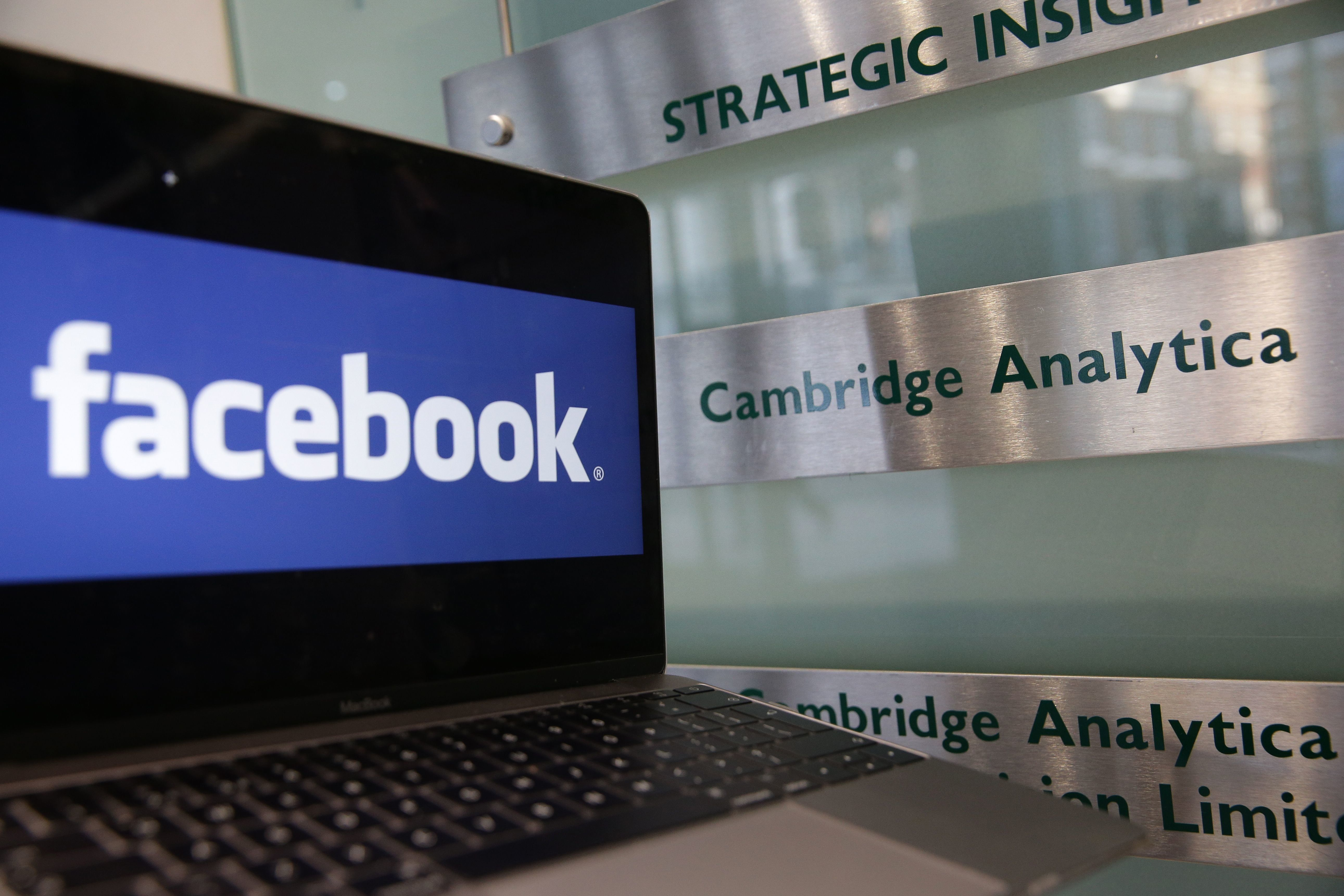 A laptop showing the Facebook logo is held alongside a Cambridge Analytica sign at the entrance to the building housing the offices of Cambridge Analytica, in central London on March 21, 2018.  Facebook expressed outrage over the misuse of its data as Cambridge Analytica, the British firm at the centre of a major scandal rocking the social media giant, suspended its chief executive.  / AFP PHOTO / Daniel LEAL-OLIVAS        (Photo credit should read DANIEL LEAL-OLIVAS/AFP/Getty Images)