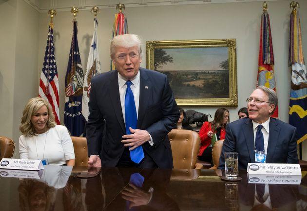 President Donald Trump takesa seat between White and National Rifle Associationleader Wayne...