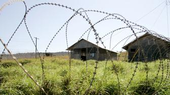 Interrogation buildings at Camp X-Ray, the first location where detainees were held at the United States Naval Base in Guantanamo Bay, Cuba, stand empty and overgrown January 17, 2006. The detainees held in Guantanamo were captured early in the war in Afghanistan and were held in the temporary facility until Camp Delta could be completed. About 500 detainees are being held on the U.S. base. REUTERS/Joe Skipper