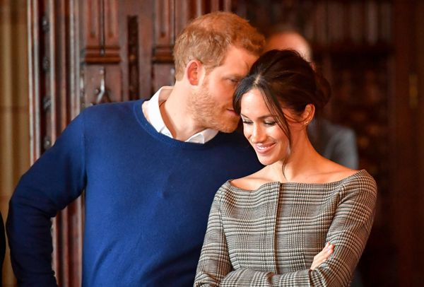 Harry whispers to Meghan as they watch a performance by a Welsh choir during a visit to Cardiff Castle on Jan. 18.