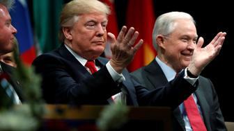U.S. President Donald Trump, seated with Attorney General Jeff Sessions, acknowledges applause from the audience as he participates in a graduation ceremony at the FBI Academy on the grounds of Marine Corps Base Quantico in Quantico, Virginia, U.S. December 15, 2017.  REUTERS/Jonathan Ernst