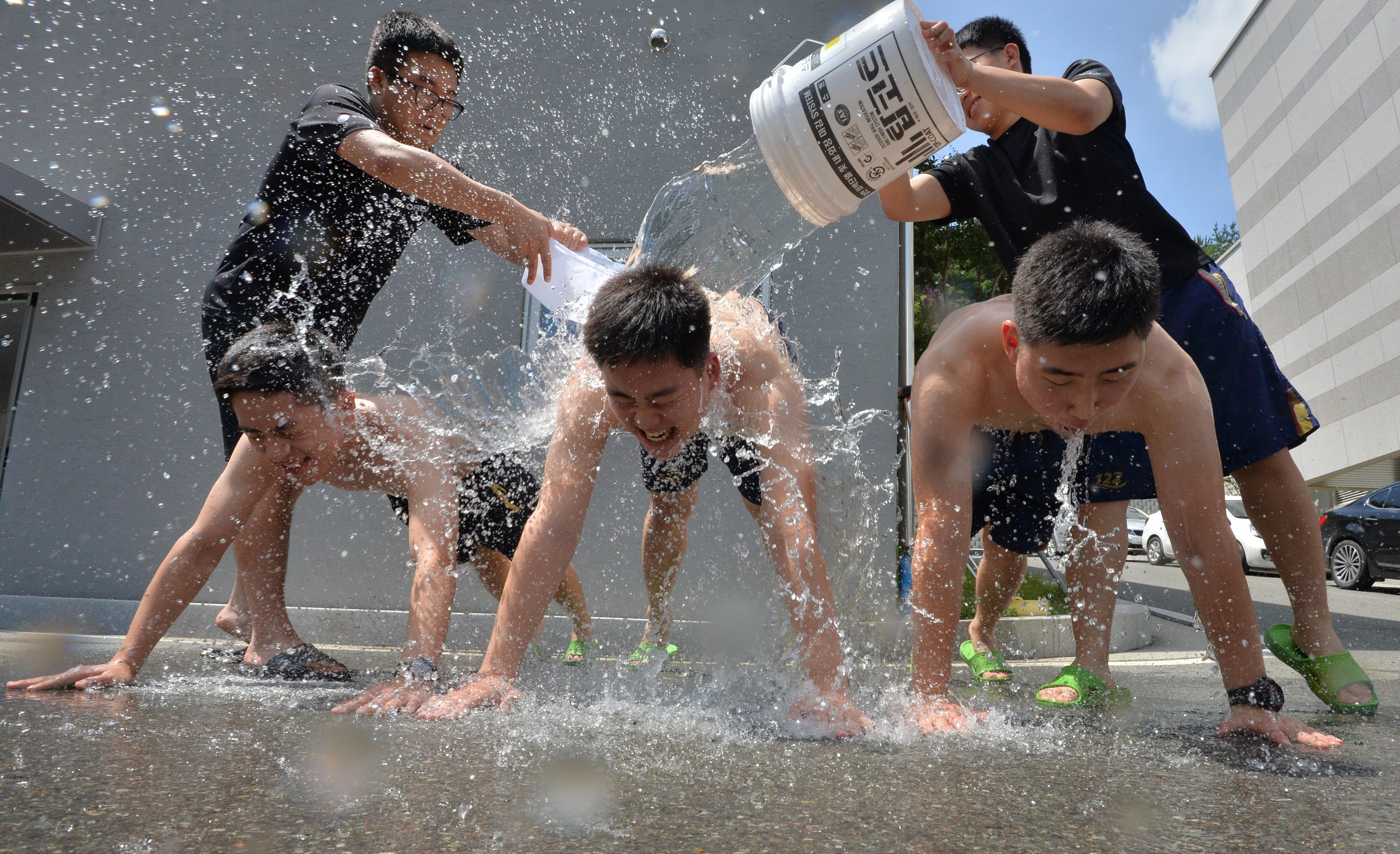 전국 대부분의 지역에 폭염주의보가 발효된 12일 오후 경북 포항해양경찰서 소속 의경대원들이 점심 휴식시간을 이용해 등목을 하고 있다.
