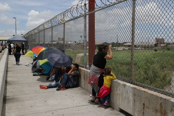A Honduran mother and her 3-year-old daughter wait with fellow asylum-seekers on the Mexican side of the Brownsville-Matamoro