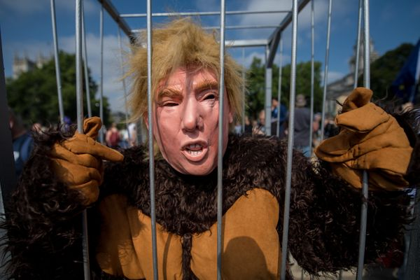 A man dressed as Trump in a gorilla costume stands in what appears to be a prison cell during a London protest.