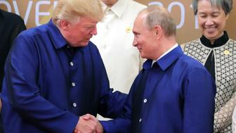 US President Donald Trump (L) shakes hands with Russia's President Vladimir Putin (R) as they pose for a group photo ahead of the Asia-Pacific Economic Cooperation (APEC) Summit leaders gala dinner in the central Vietnamese city of Danang on November 10, 2017. / AFP PHOTO / SPUTNIK / Mikhail KLIMENTYEV        (Photo credit should read MIKHAIL KLIMENTYEV/AFP/Getty Images)