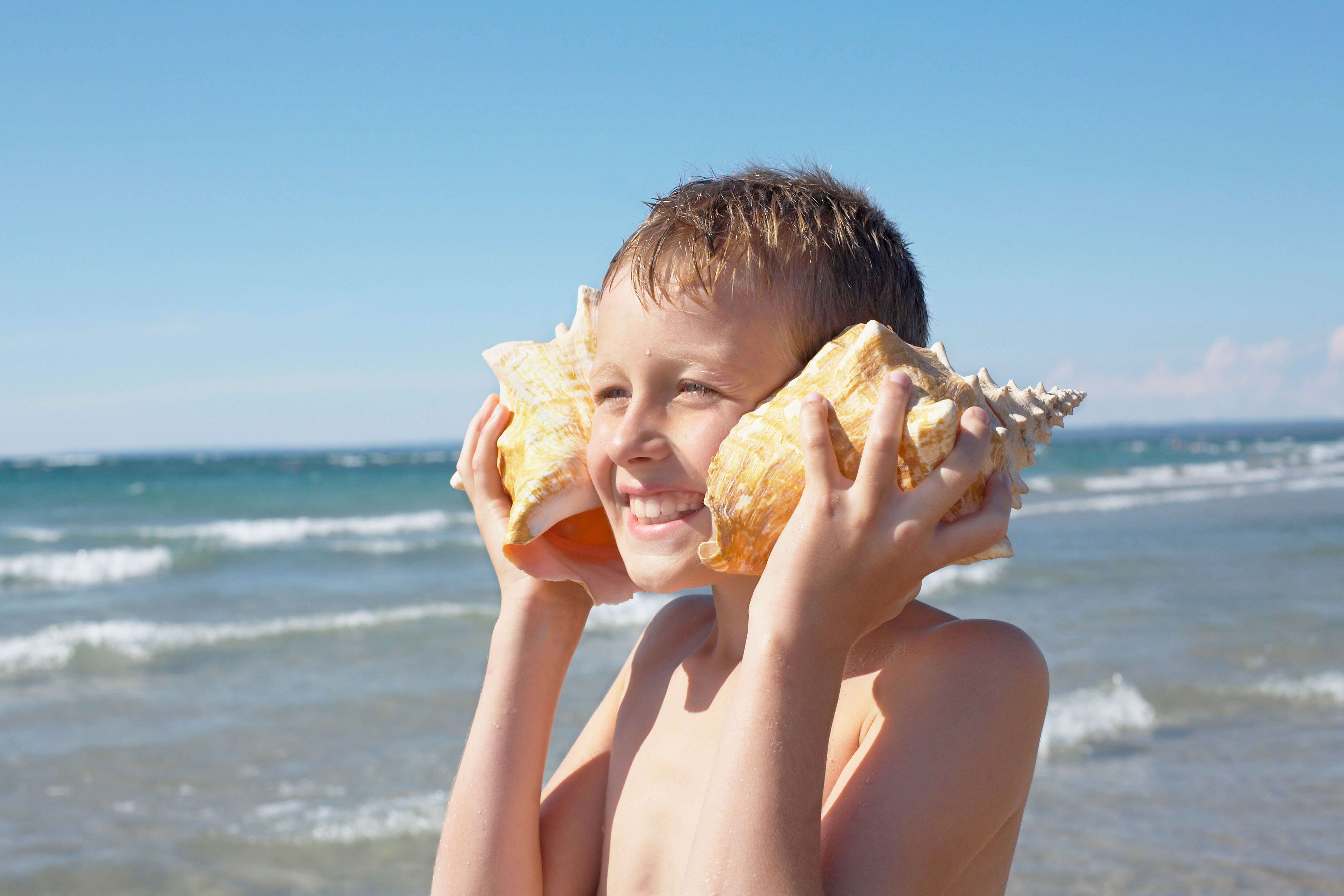 Boy Holding Seashells to His Ears, Elmvale, Ontario, Canada