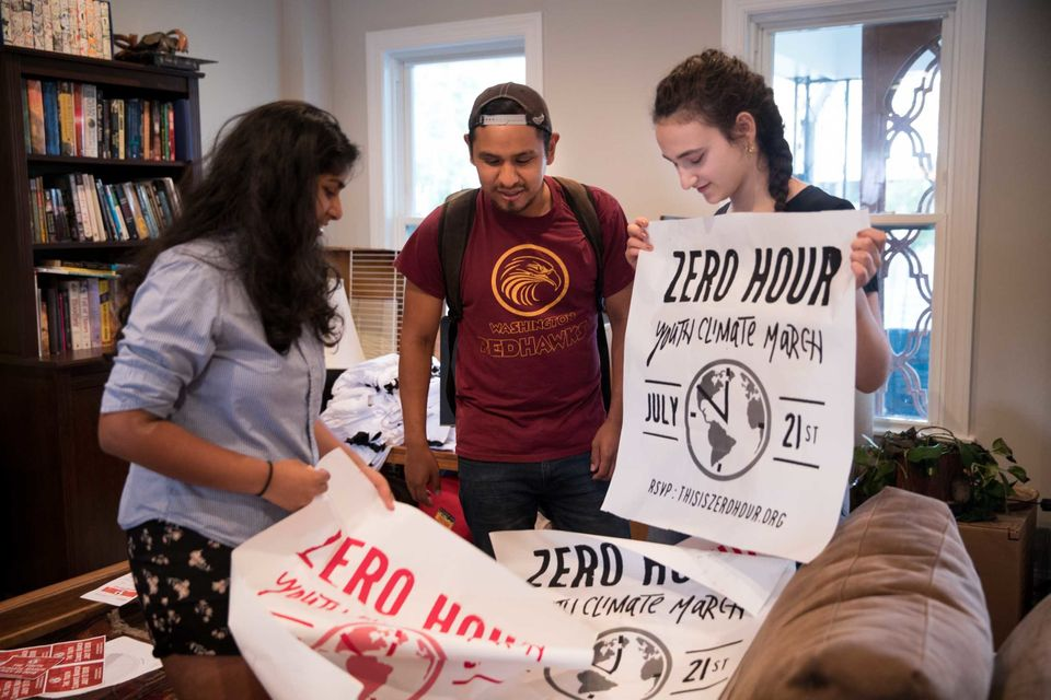 Jair Carrasco, center, shows new posters to Jamie Margolin and Nadia