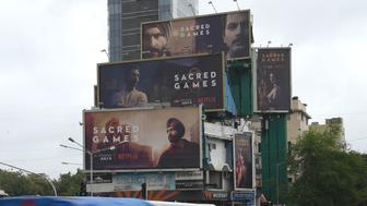 This photo taken on July 4, 2018 shows Indian commuters travelling past large billboards for 'Sacred Games', the upcoming Indian series on Netflix, in Mumbai. - Netflix's first original Indian series released on July 6 as the US streaming giant battles with Amazon Prime for a slice of India's fast growing on-demand video market. (Photo by INDRANIL MUKHERJEE / AFP) / To go with INDIA-US-ENTERTAINMENT-INTERNET-TELEVISION-NETFLIX,FOCUS by Peter HUTCHISON        (Photo credit should read INDRANIL MUKHERJEE/AFP/Getty Images)